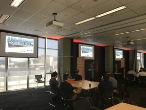 The podium and tc screens at the back of the hack room